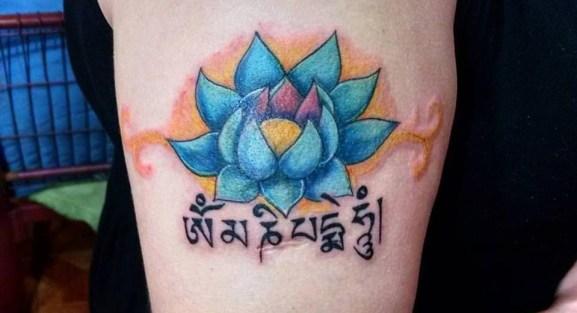 """Tatuagem da Aline Chuvas: A flor de lótus, que simboliza o nascimento, a sabedoria. A lótus é um símbolo de grande força, afinal, a lótus precisa nascer no fundo da lama e então subir para a superfície da água. Abaixo está o mantra OM MANI PADME HUM. Um mantra que significa """"da lama nasce a flor de lótus"""", mas há também quem diga que significa """"saúdo a joia da lótus"""". O fato é que o mantra vibra uma energia maravilhosa de cura, alinhamento espiritual e nos ajuda a ter paciência e sabedoria."""