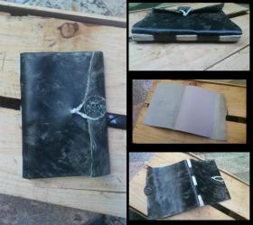 Caderno A5, papel jornal, capa flexivel de couro e costura aparente em barbante.