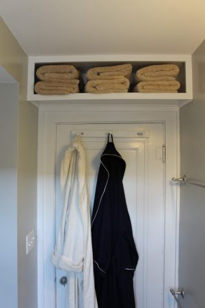 Create more storage space in a tiny bathroom by installing shelves over the top of the door.