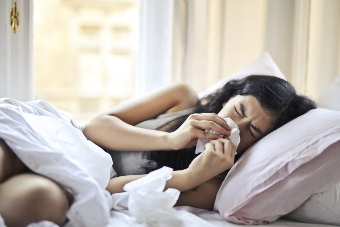 woman-lying-on-bed-while-blowing-her-nose