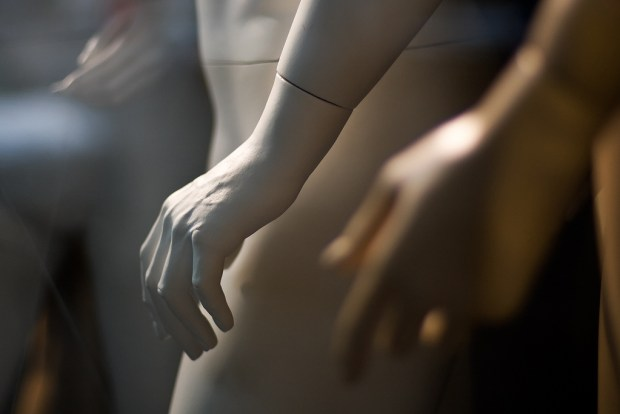 A white plastic mannequin hand lit from the upper left side of the image in a store window. Two other palms are visible out of focus in the foreground and background.
