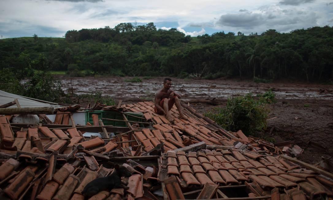"""""""Tudo estava tremendo e vi enormes árvores e pessoas desaparecendo sob a lama"""", disse Emerson dos Santos, sentado no telhado da casa de sua família para proteger o que restou de seus pertences de saqueadores MAURO PIMENTEL / AFP"""