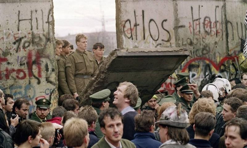 Multidão em frente o Muro de Berlim enquanto guardas da fronteira da Alemanha Oriental derrubam parte da barreira, criado um novo ponto de travessia entre Berlim Ocidental e Berlim Oriental Foto: GERARD MALIE / AFP/11-11-1989