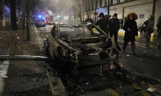 Pessoas caminham entre os destroços de um carro em chamas durante uma manifestação em Paris Foto: GEOFFROY VAN DER HASSELT / AFP