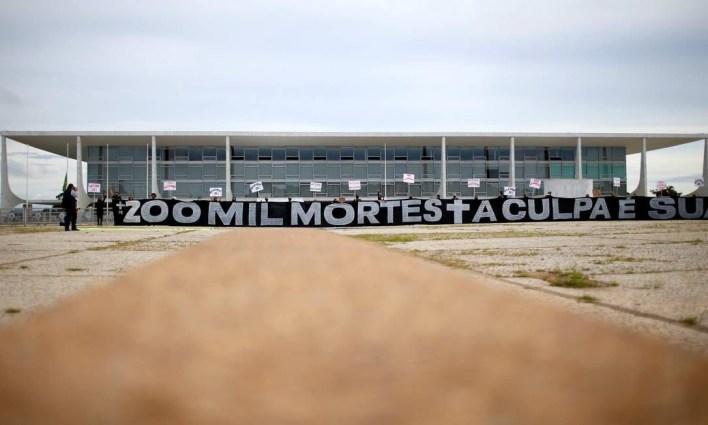 """Manifestantes exibem faixa com a frase """"Mais de 200 mil mortes, a culpa é sua Bolsonaro"""" em frente ao Palácio do Planalto, em Brasília, na manhã desta sexta-feira (8) Foto: ADRIANO MACHADO / REUTERS"""
