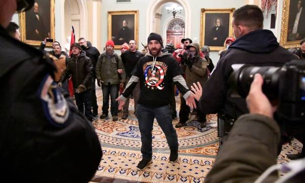 DOUG JENSEN, 41, an Iowa resident, was arrested by the FBI early on Saturday.  Doug was recognized in imagery that became iconic during the Capitol riot.  He is the man who, wearing a knit cap and a QAnon T-shirt with an eagle, appears with open arms facing Congress security. Photo: MIKE THEILER / REUTERS