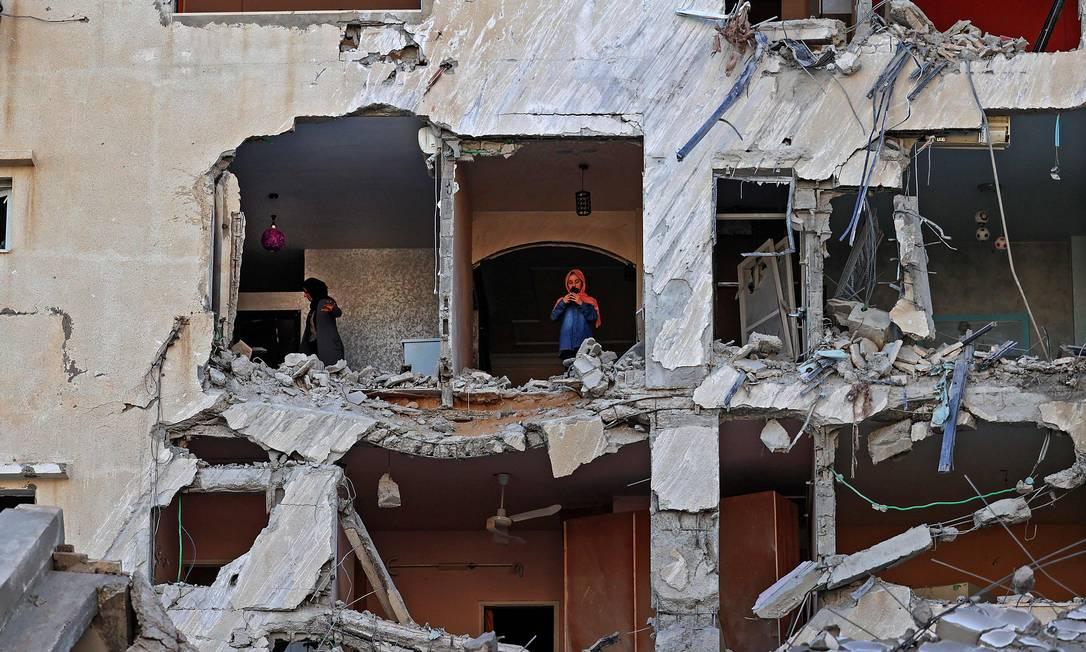 Mulheres palestinas verificam os danos dentro de um apartamento em um prédio fortemente danificado na Cidade de Gaza Foto: MOHAMMED ABED / AFP