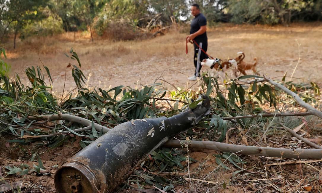 Um homem israelense passa pelos restos de um foguete disparado pelo grupo islâmico palestino Hamas da Faixa de Gaza e que foi destruído pelo sistema de defesa aérea de Israel, em Ashkelon Foto: JACK GUEZ / AFP