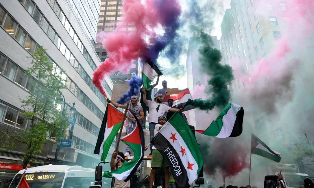 Manifestantes seguram bandeiras da Palestina e da Síria em apoio à Palestina no centro de Manhattan, na cidade de Nova York, EUA Foto: ANGELA WEISS / AFP - 18/05/2021