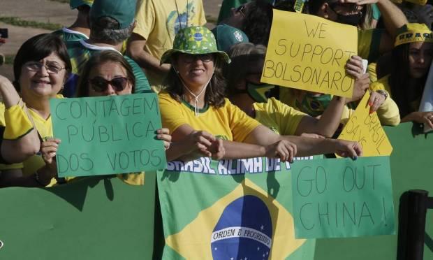 "Next to the Brazilian flag, a sign reads: ""Outside China""  Photo: Cristiano Mariz / O Globo"