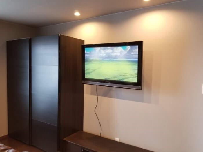 寝室の壁掛けテレビ。ケーブルがぶらさがっている