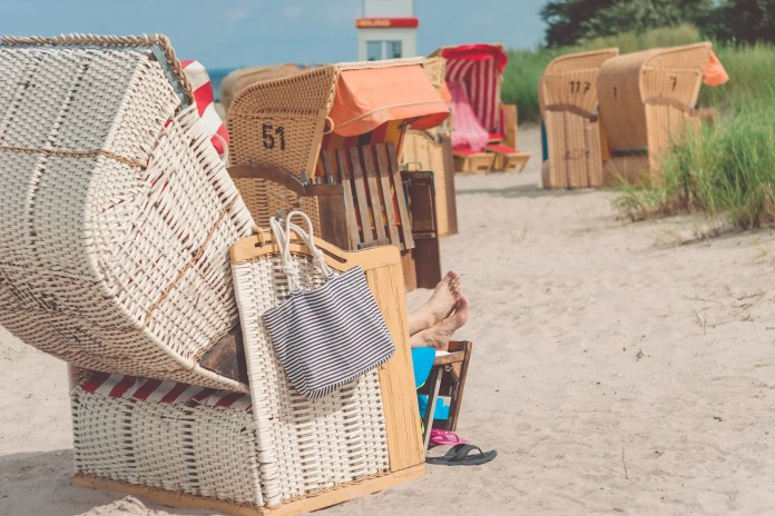 Tourist resting relax in striped roofed chairs on sandy beach in Travemunde., Lubeck, Germany
