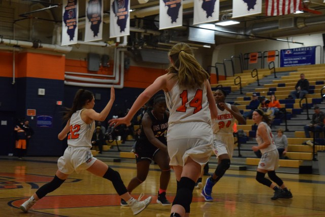 Three OHS basketball players (22, 14, and 24) run for the ball.