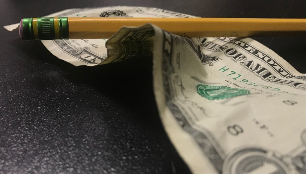 Crumpled dollar bill and pencil.