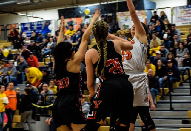Two Yorkville girls basketball players (10 and 21) guard an OHS player (15)