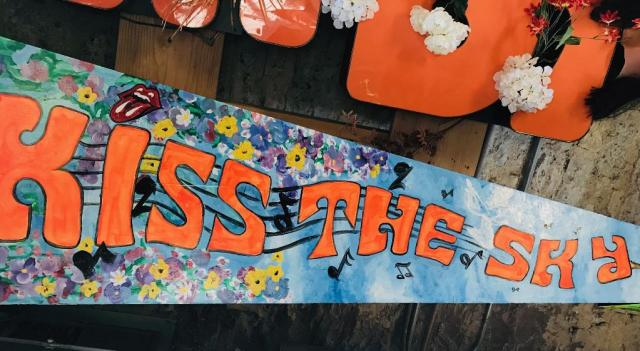 "A painted pennant reading ""Kiss The Sky"""