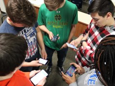 Students standing in a circle, looking at their cell phones