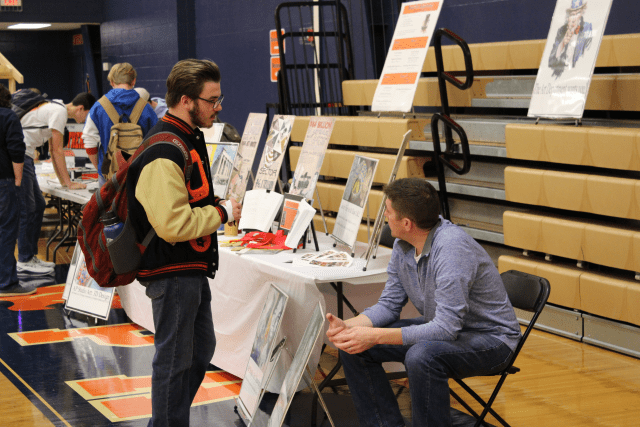 A student browses a table at the elective fair. Aaron Kolkay, an art teacher, talks to the student.