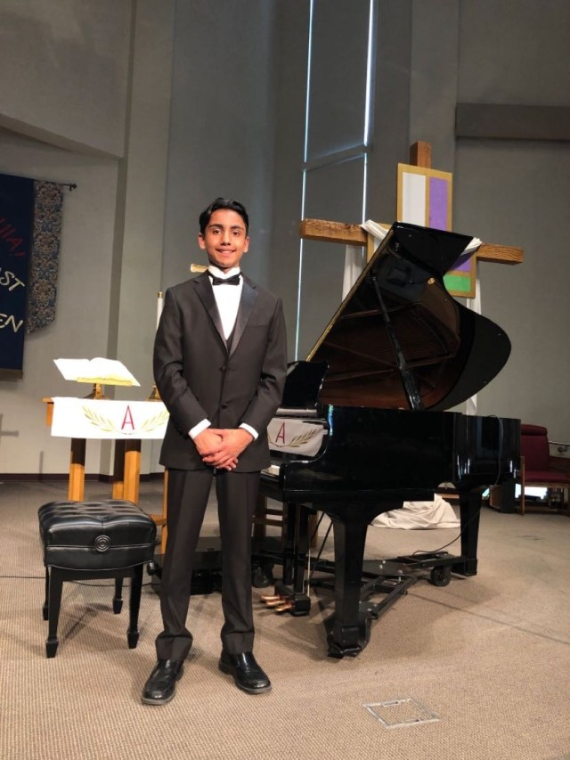 Iyer in front of a grand piano on stage after one of his recitals.