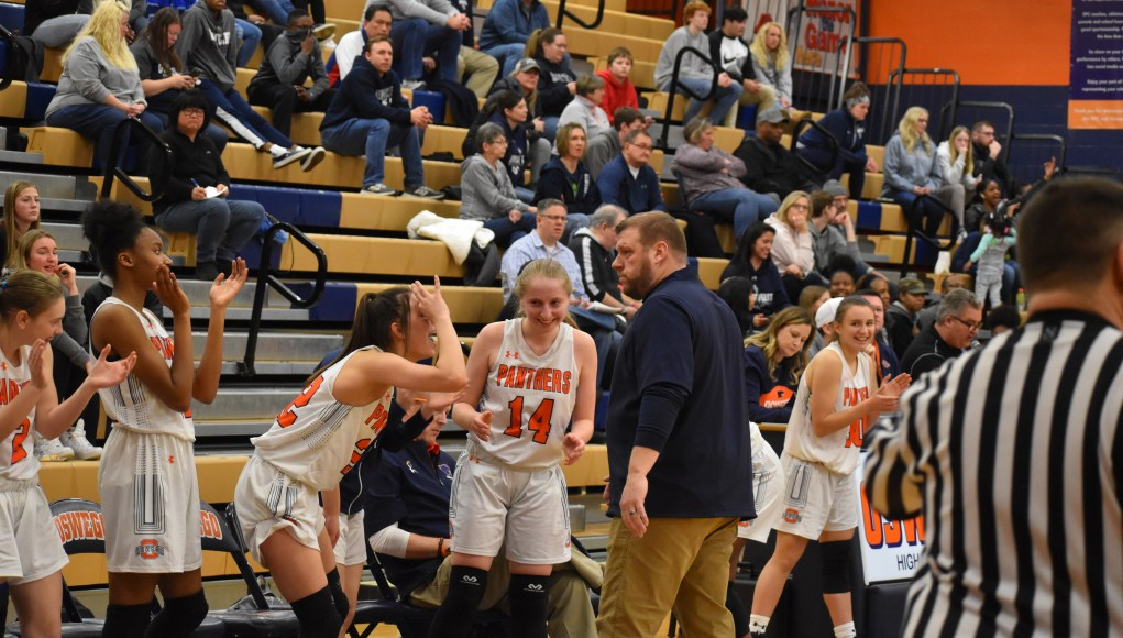The Oswego High School Girls Basketball team celebrates a three-pointer made by senior Lukrecija Juozeviciute