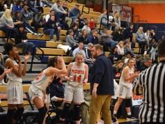 The Oswego High School Girls Basketball team celebrates a three-pointer made by senior Lukrecija Juozeviciute
