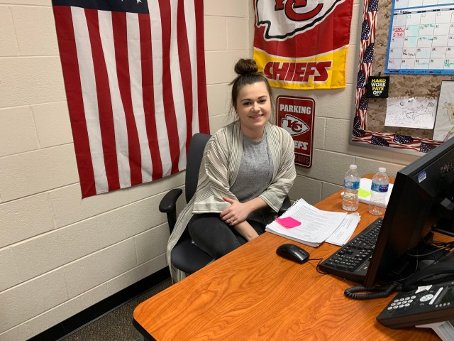 Rachel Spolum poses for a picture at her desk