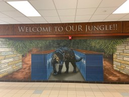 "A mural which reads ""Welcome to Our Jungle,"" featuring a panther walking between two rows of lockers."