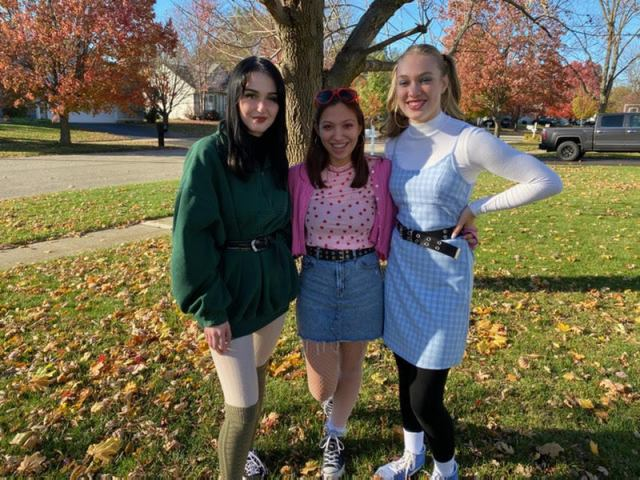 Three Oswego High School girls posing for a picture together in Halloween costumes.