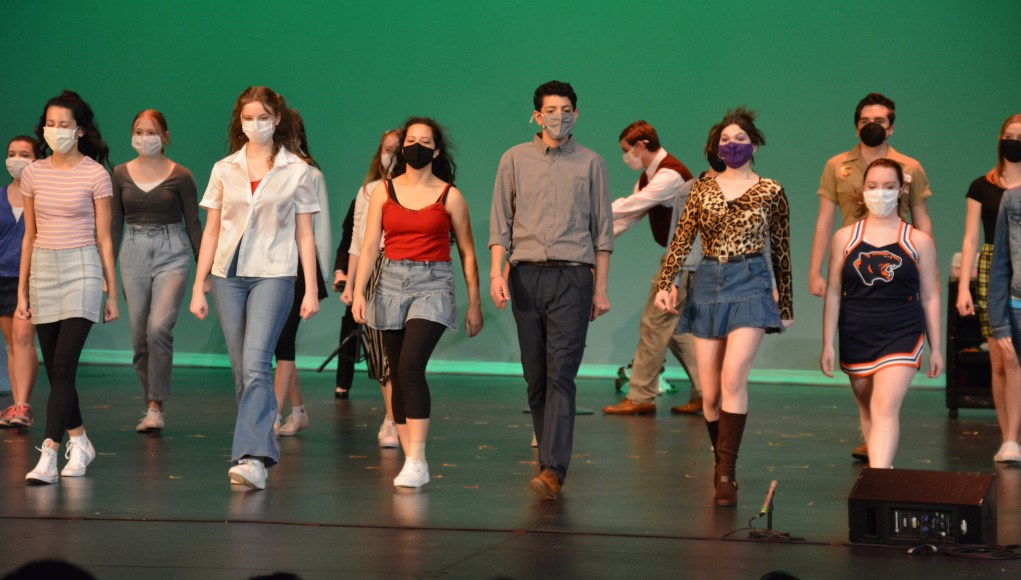 Cast members wearing masks walk to the front of the stage together