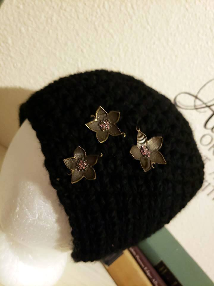 crochet black beanie with bronze and pink flower embellishments