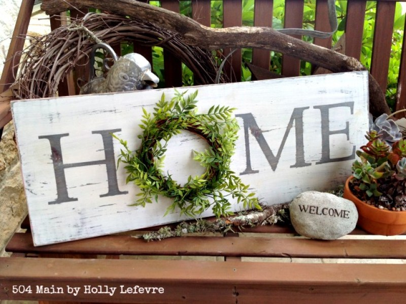 DIY Farmhouse Style Home Sign With a Wreath. 14 DIY Farmhouse Signs you can make on a small budget. Farmhouse decor can cost a lot but these rustic wood signs are affordable to make. If you love Joanna Gaines than you have to try these projects! Guide to how to make a farmhouse sign, farmhouse signs for kitchen, bathroom farmhouse sign DIY, DIY wood signs, Farmhouse Sign Decor, Make you own farmhouse sign, farmhouse signs DIY guide