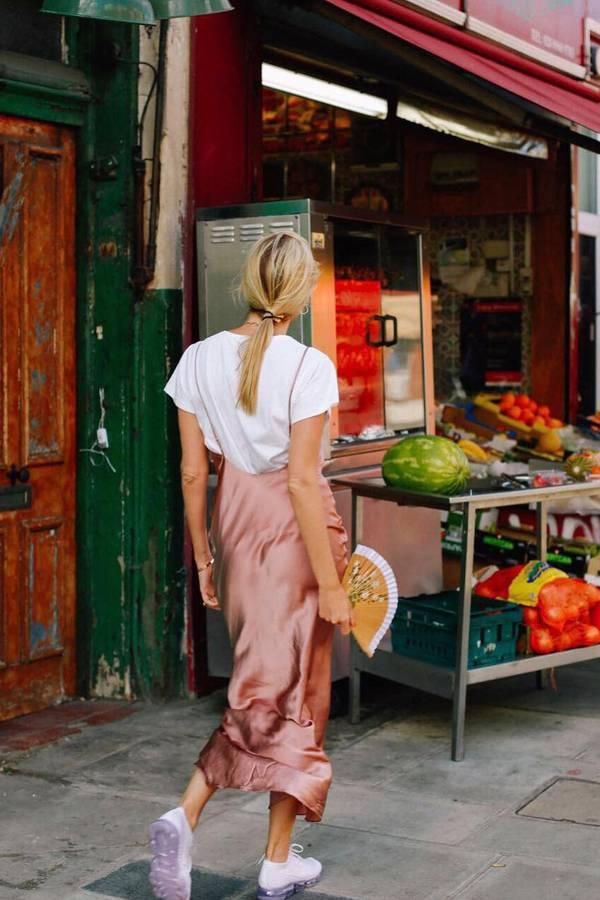 Девушка в розовом платье комбинация, белая футболка и белые кроссовки