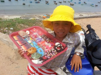 Young girl selling trinkets along the waterfront in Vietnam.
