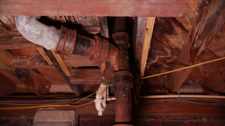Close up of rusty pipes in crawl space