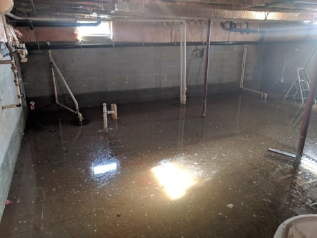 Interior of flooded basement with sunbeams