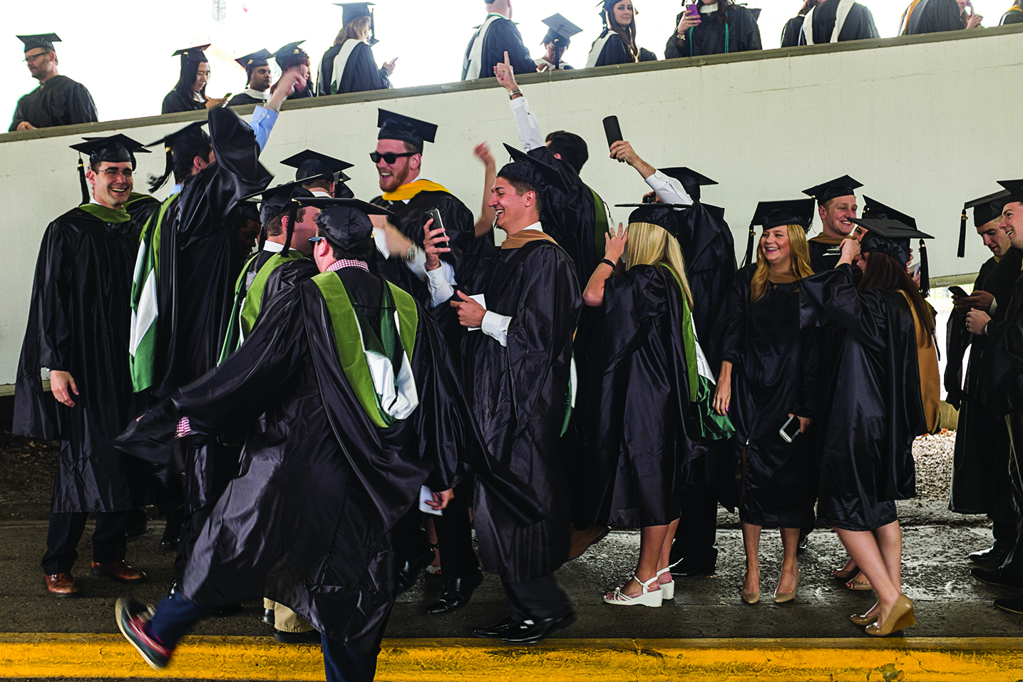 Students from Sports Administration in the College of Business get down to the sounds of a Bluetooth speaker before the start of Ohio University's Graduate Commencement on Friday, May 1, 2015. Photo by Rob Hardin / Rob Hardin