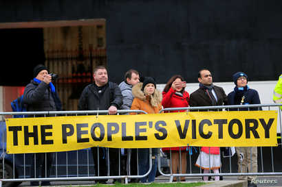 People stand behind a banner supporting the results of the general election, in London, Britain, December 13, 2019. REUTERS…