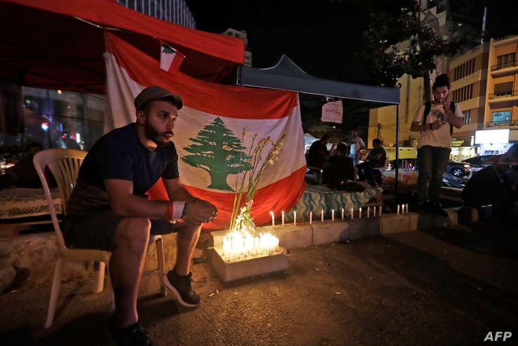 TOPSHOT - Lebanese protesters hold a candlelight vigil during ongoing anti-government demonstrations in Lebanon's capital…