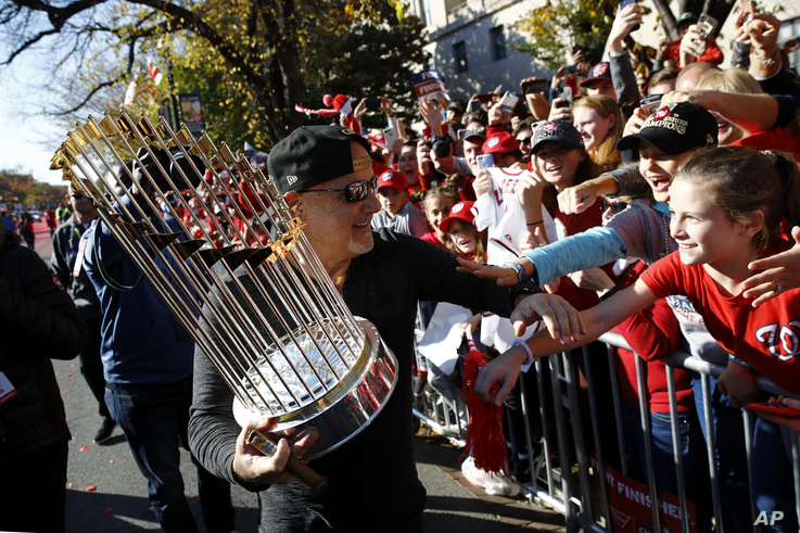 Washington Nationals general manager Mike Rizzo shows off the World Series trophy to cheering fans during a parade to celebrate…