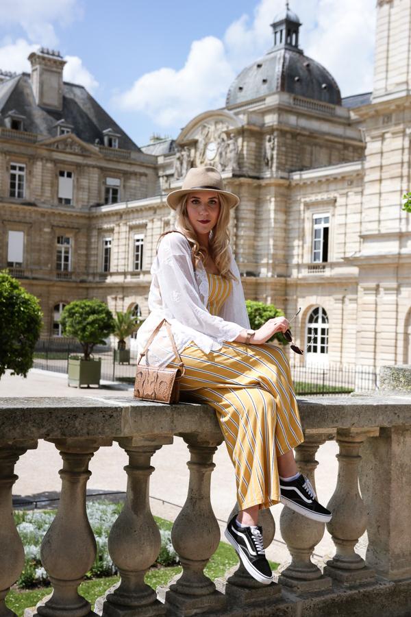Blogueuse mode vêtue d'une combinaison jaune à rayures