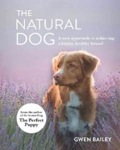 The cover of The Natural Dog features a soft focus of a light brown and white medium-sized dog standing in a field of lavender.
