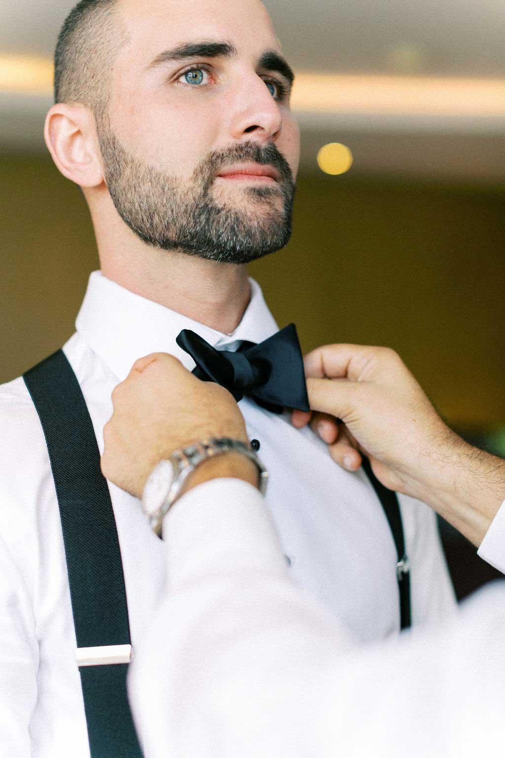 Groomsman fixes groom's bowtie