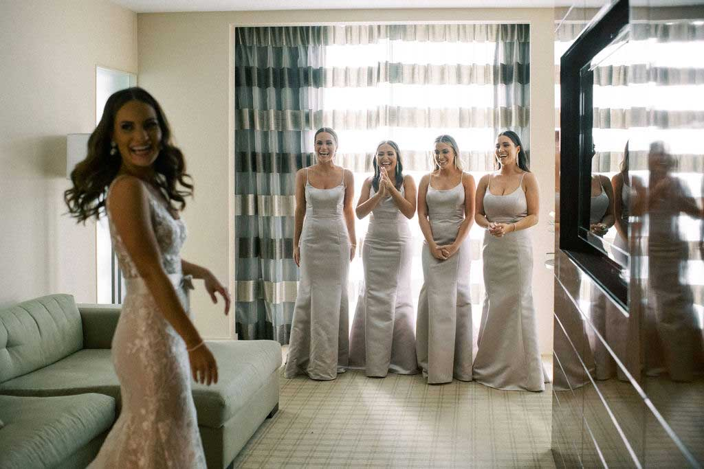 bride reveals her dress to bridesmaids and looks back at the camera.