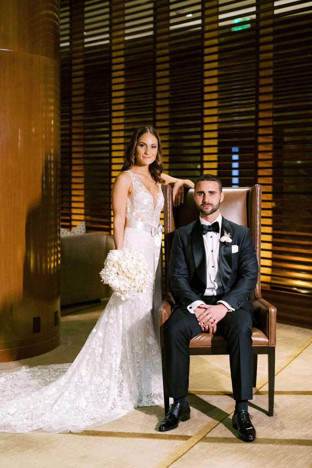 groom sits on chair and bride places arm on chair holding her bouquet.