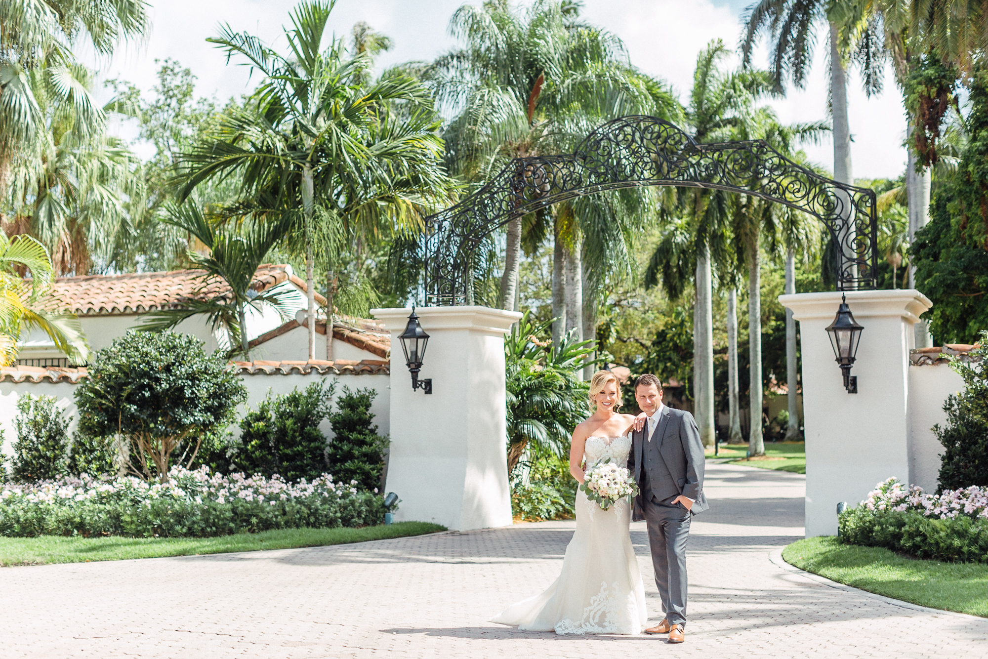 Couple stands and smiles outside gate entrance at the Fisher Island Club.