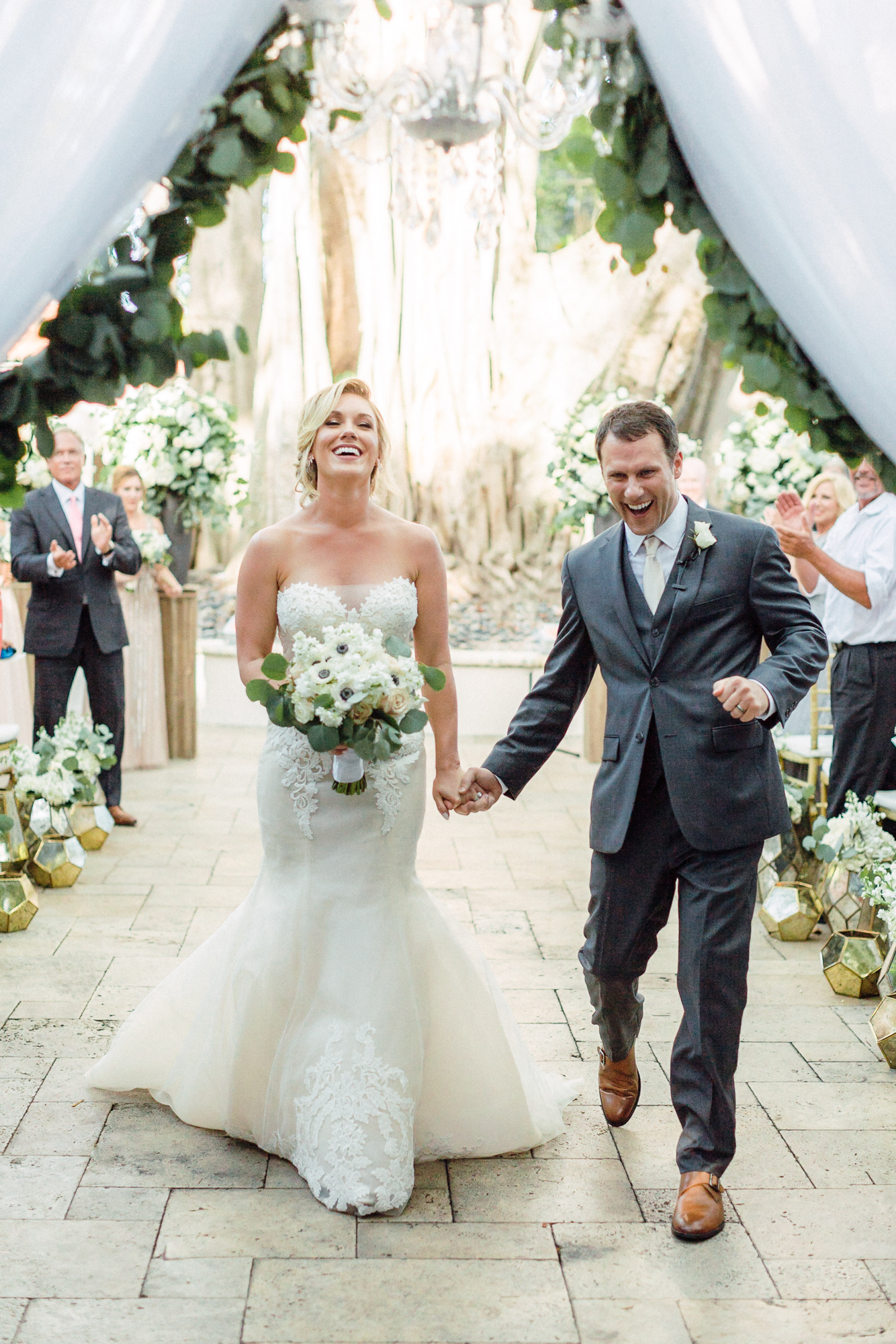 Newlywed couple walk down the aisle in their outdoor ceremony space.