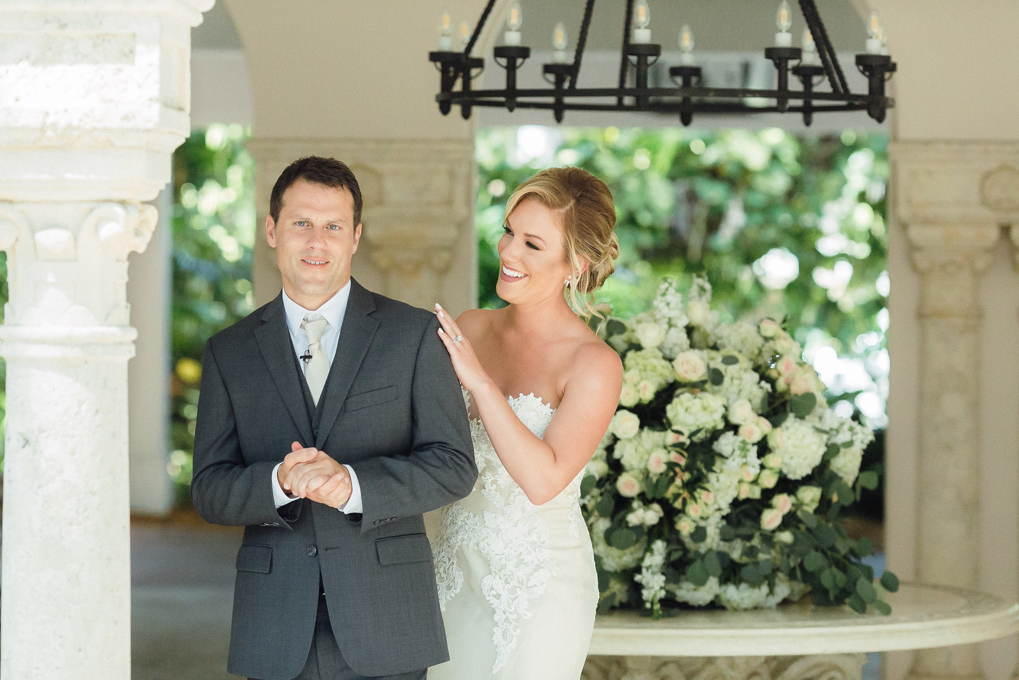 Bride stands behind groom and smiles at him while grooms smiles at camera for their first looks at Fisher Island Club.