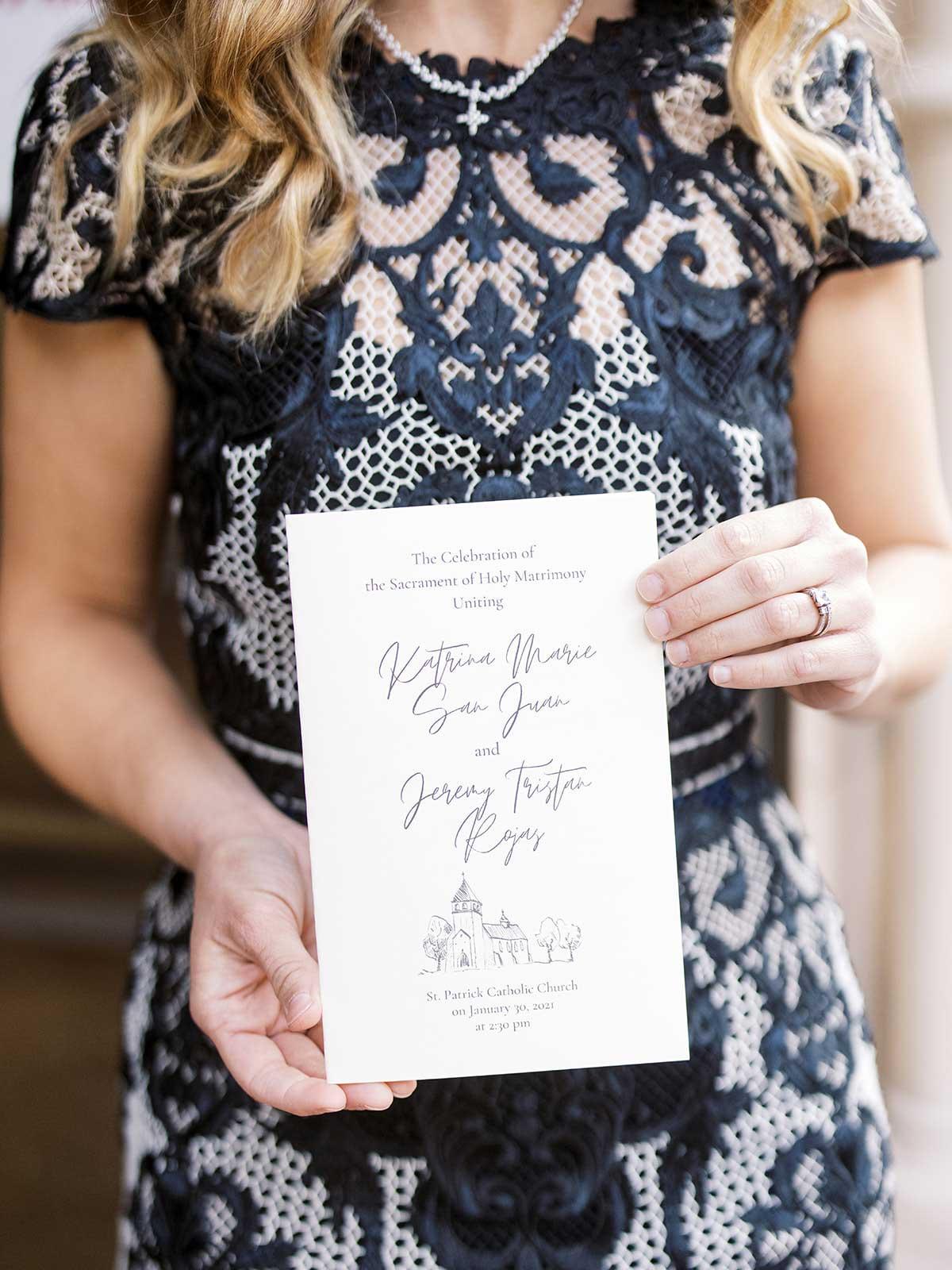 guest holding wedding invitation.