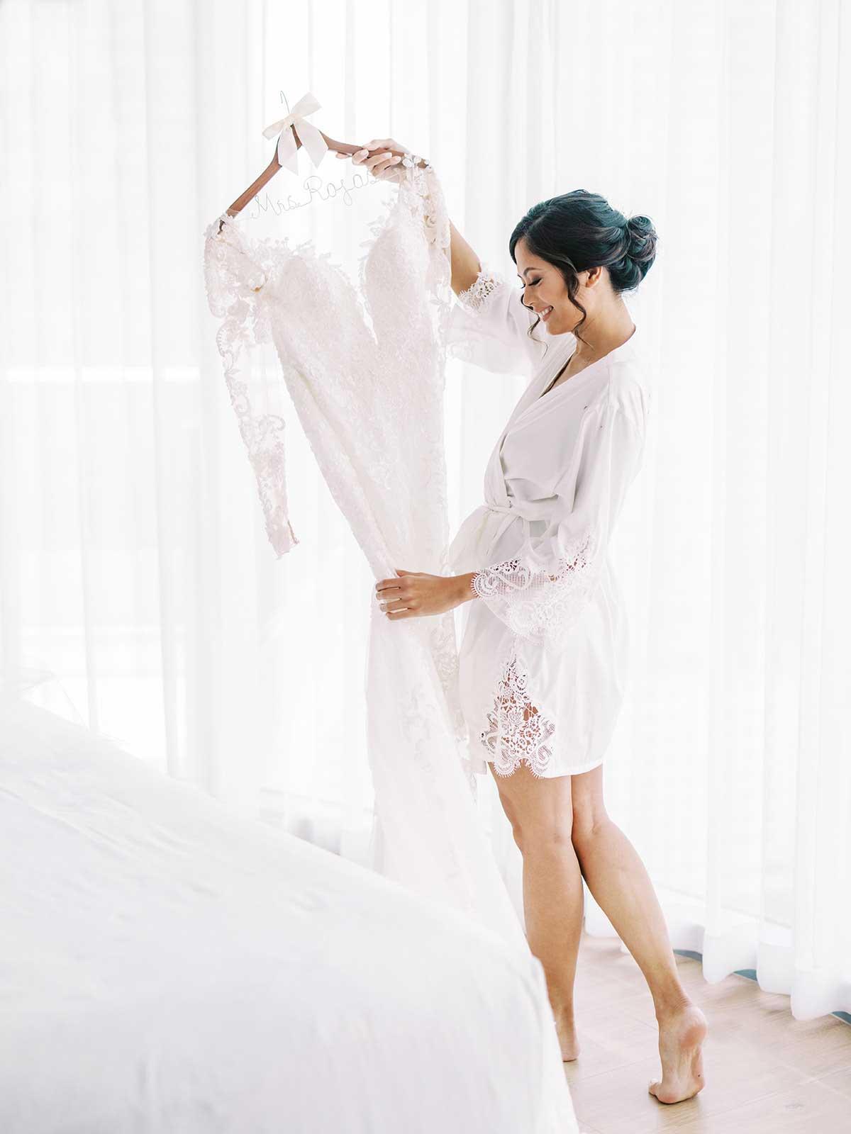bride admiring her wedding gown wearing her white robe.