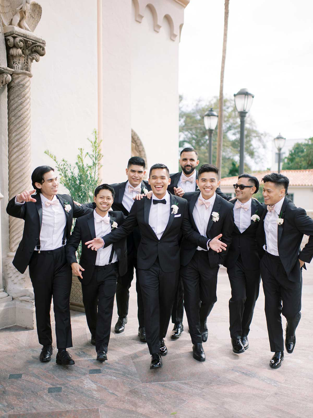 groom and groomsmen walk towards camera for a candid photo.